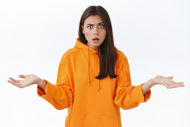 Verwirrte und sauere junge verwirrte frau in orangefarbenem hoodie, die frustriert mit verblüfftem ausdruck anstarrt, mit den schultern zuckend die hände vor bestürzung ausbreitet, weiß nicht, warum die person wütend ist