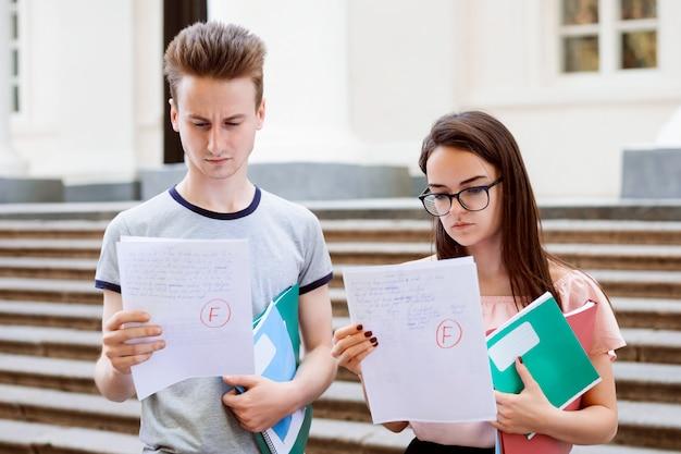 Verwirrte und traurige studenten, die papiere mit schlechten testergebnissen halten