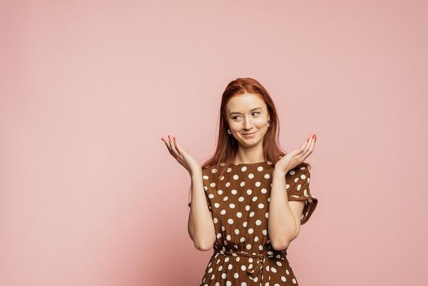 Verwirrte und verwirrte frau an einer rosa wand. ein mädchen in einem schönen braunen kleid zeigt die emotion, nicht zu verstehen.