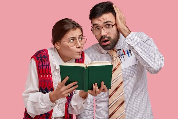 Verwirrte ungeschickte weibliche und männliche leser schauen sich das lehrbuch an, haben besorgte ausdrücke, stopfen material