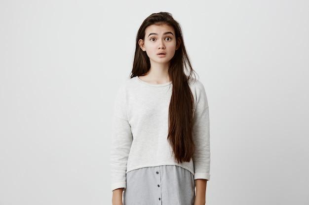 Verwirrte verwirrte frau, lässig gekleidet mit langen dunklen haaren, über den nächsten schritt nachdenkend, nicht wissend, was zu tun ist. menschliches gefühl, emotionen, gesichtsausdrücke