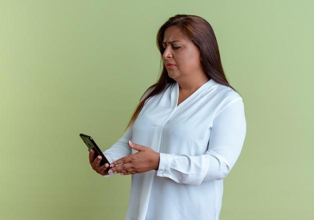 Verwirrte zufällige kaukasische frau mittleren alters, die telefon hält und betrachtet