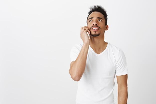 Verwirrter afroamerikaner kerl im weißen t-shirt, das auf handy spricht, verwirrt oder unsicher nach oben schaut