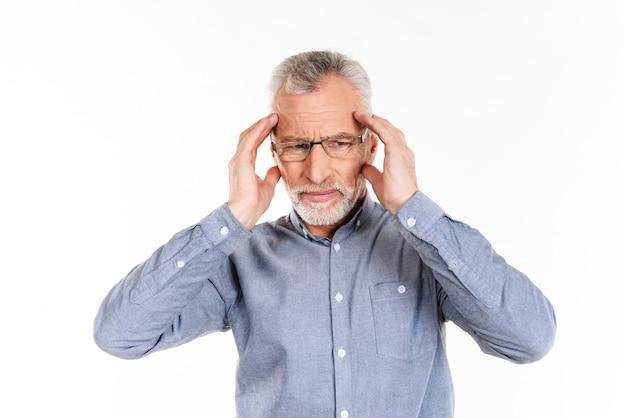Verwirrter alter mann hat kopfschmerzen und hält seinen kopf