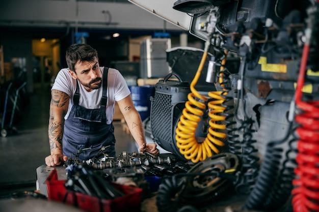 Verwirrter arbeiter in overalls, der sich auf einen lastwagen stützt und versucht, ihn zu reparieren. firma für import und export.