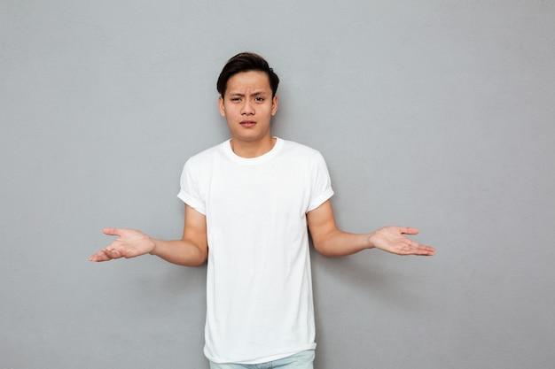 Verwirrter asiatischer mann, der über graue wand steht