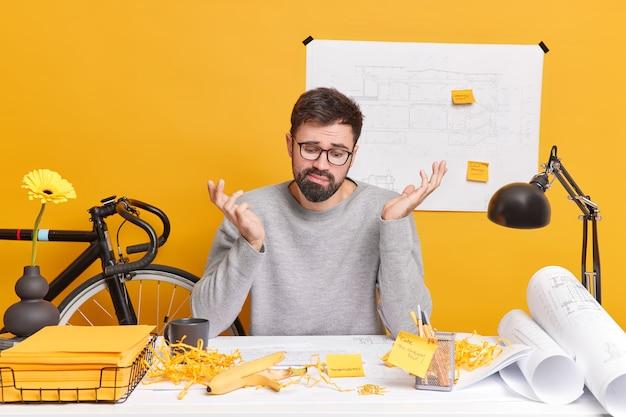 Verwirrter bärtiger erwachsener mann sieht zweifelhaft auf architekturskizze zuckt mit den schultern, da er nicht weiß, wie man ihn verbessern kann, verbringt viel zeit mit der arbeit sitzt am desktop mit blaupausen für zukünftige projekte for