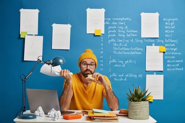 Verwirrter bärtiger freiberuflicher arbeiter entwickelt startup-projekt, isst zu mittag, isst köstlichen snack, hält papierdokument in der hand, posiert am desktop.