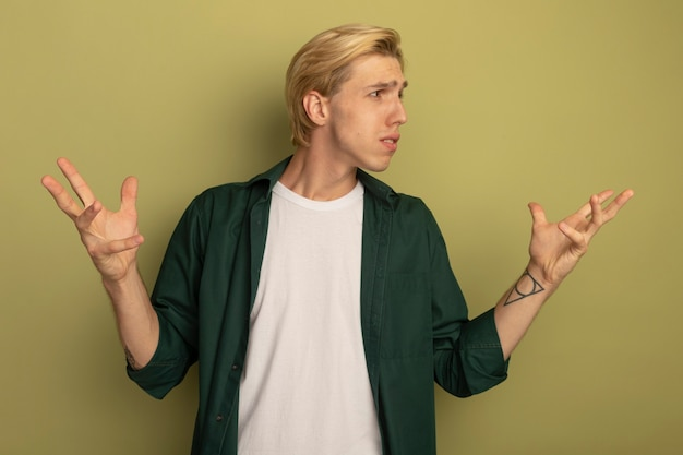Verwirrter blick auf den jungen blonden mann der seite, der grünes t-shirt trägt, das hände ausbreitet