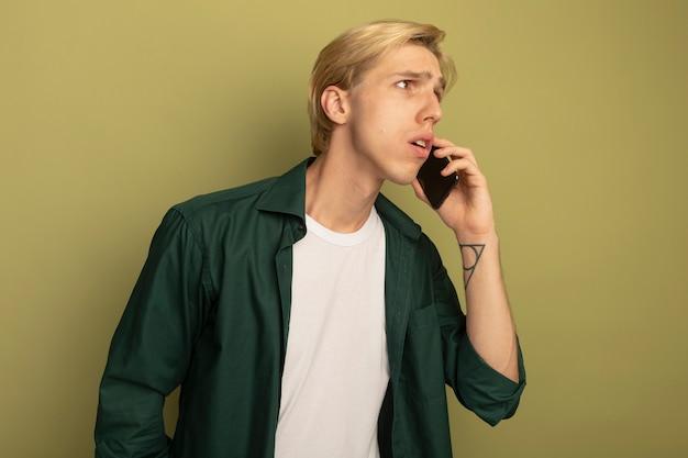 Verwirrter blick auf seite junger blonder kerl, der grünes t-shirt trägt, spricht am telefon
