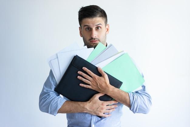 Verwirrter büroangestellter, der stapel von dokumenten hält