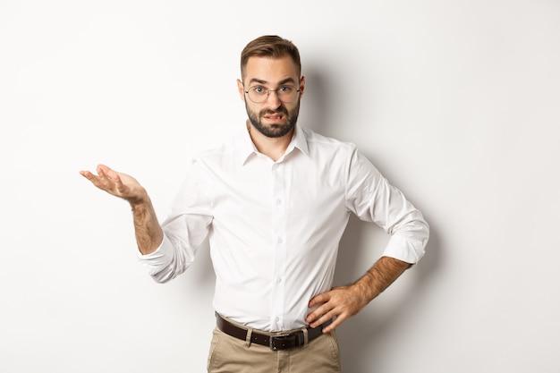 Verwirrter büroangestellter zuckt die achseln, kann etwas nicht verstehen und steht über weißem hintergrund.