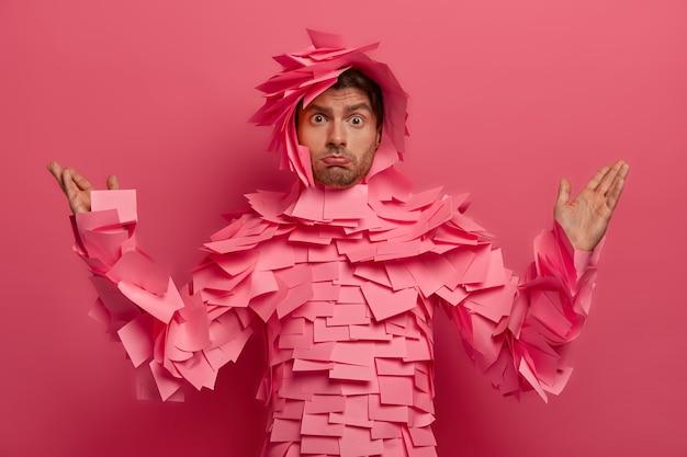 Verwirrter empörter unrasierter mann hebt die hände, spitzt die unterlippe, schaut mit missfallenem gesichtsausdruck, bedeckt von haftnotizen, isoliert auf rosa wand, unzufrieden etwas unangenehmes zu hören
