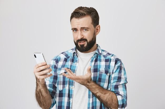 Verwirrter enttäuschter erwachsener mann, der auf seltsame app auf smartphone reagiert