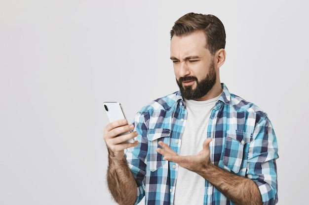Verwirrter enttäuschter erwachsener mann, der smartphonebildschirm betrachtet