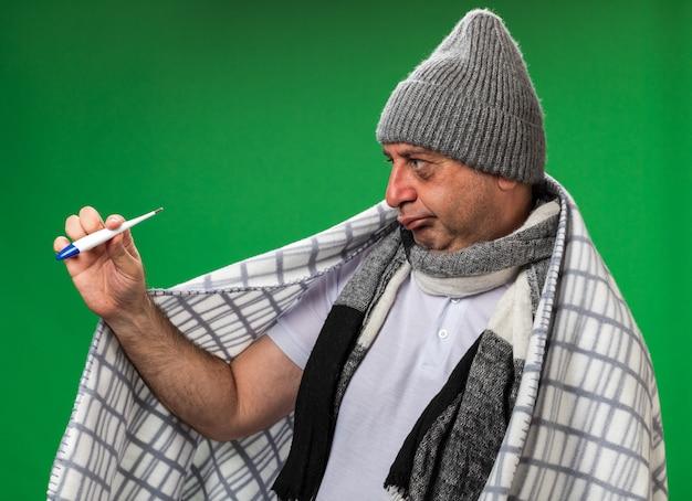 Verwirrter erwachsener kranker kaukasischer mann mit schal um den hals, der eine wintermütze trägt, die in kariertes halten gewickelt ist und das thermometer isoliert auf grüner wand mit kopienraum betrachtet