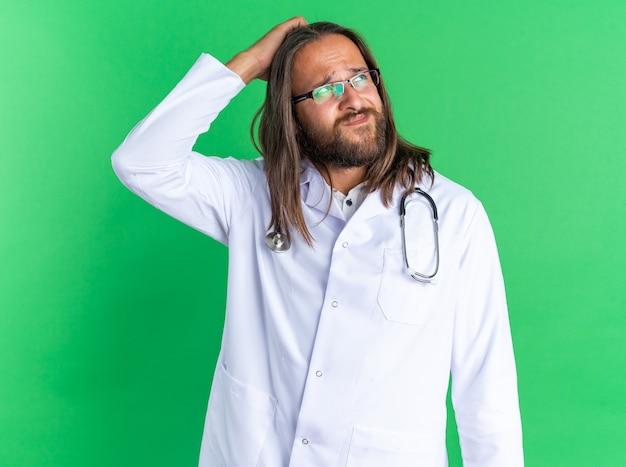 Verwirrter erwachsener männlicher arzt, der medizinische robe und stethoskop mit brille trägt, die nach oben schaut und den kopf isoliert auf grüner wand kratzt
