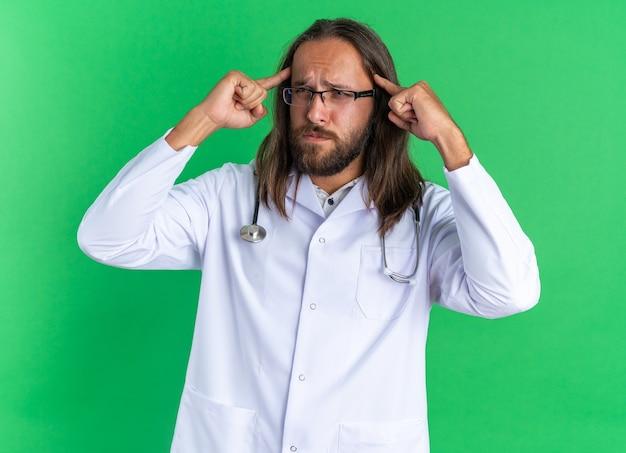 Verwirrter erwachsener männlicher arzt mit medizinischem gewand und stethoskop mit brille, der auf die seite schaut und eine denkgeste isoliert auf grüner wand macht