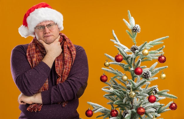 Verwirrter erwachsener mann mit brille und weihnachtsmütze mit schal um den hals, der in der nähe des geschmückten weihnachtsbaums steht und die hand am kinn hält, isoliert auf oranger wand