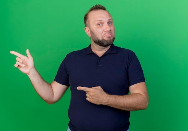 Verwirrter erwachsener slawischer mann, der lokal betrachtet und zur seite zeigt