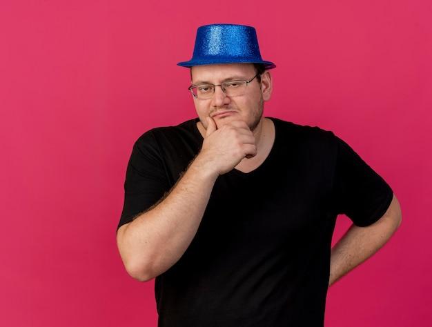 Verwirrter erwachsener slawischer mann in optischer brille mit blauem partyhut legt die hand auf das kinn und schaut in die kamera