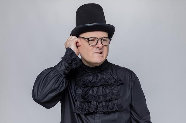 Verwirrter erwachsener slawischer mann mit zylinder und optischer brille in schwarzem gothic-hemd, der die hand auf sein gesicht legt und zur seite schaut