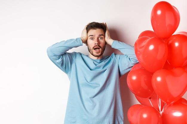 Verwirrter freund, der die hände am kopf hält und am valentinstag in panik verfällt, alarmiert mit romantischen geschenken am tag der liebenden, der in der nähe von herzballon auf weißem hintergrund steht