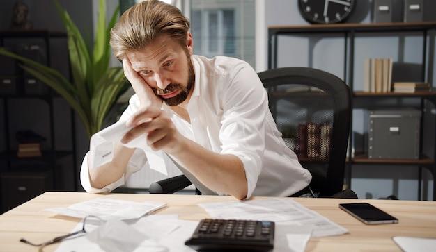 Verwirrter geschäftsmann, der am schreibtisch sitzt, mit dem kopf gegen die hand gelehnt, die rechnungen oder schecks betrachtet