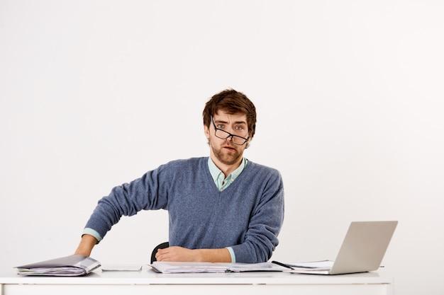 Verwirrter geschäftsmann, der am schreibtisch sitzt