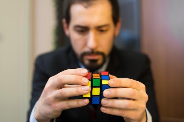 Verwirrter geschäftsmann, der versucht, einen puzzelwürfel zu lösen
