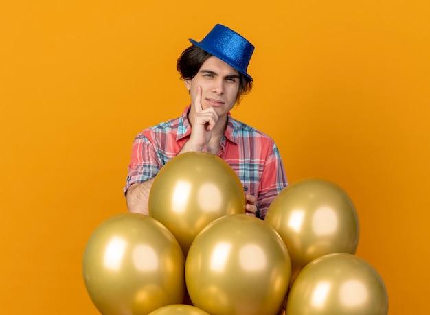 Verwirrter gutaussehender mann, der blauen partyhut trägt, legt hand auf kinn und steht mit heliumballons, die auf orange wand isoliert werden