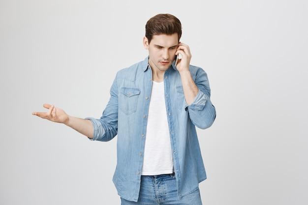 Verwirrter gutaussehender mann, der streit über telefon hat