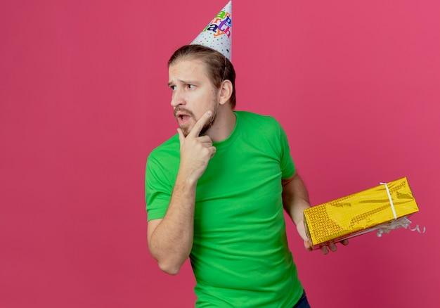 Verwirrter gutaussehender mann in der geburtstagskappe hält geschenkbox, die seite betrachtet, die auf rosa wand lokalisiert wird