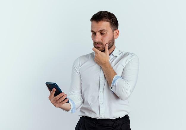 Verwirrter gutaussehender mann legt hand auf kinn, das telefon lokalisiert auf weißer wand hält und betrachtet