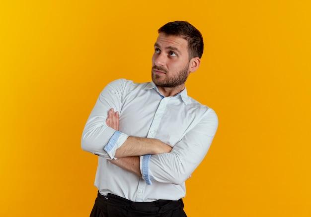 Verwirrter gutaussehender mann steht mit verschränkten armen und betrachtet seite isoliert auf orange wand