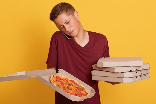 Verwirrter hart arbeitender lieferbote, der mit dem kunden telefoniert, die adresse nicht kennt, probleme hat und kartons mit pizza hält