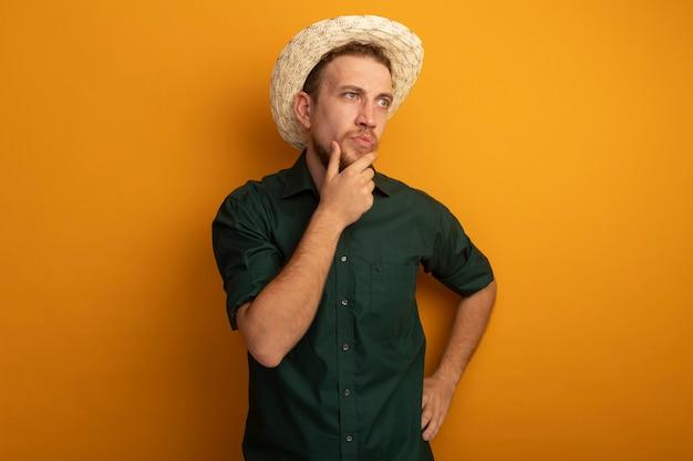 Verwirrter hübscher blonder mann mit strandhut legt hand auf kinn und schaut auf seite, die auf orange wand isoliert ist