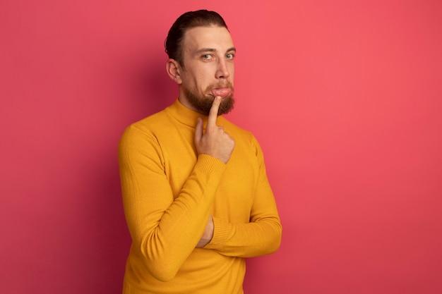 Verwirrter hübscher blonder mann zieht lippe auf rosa herunter