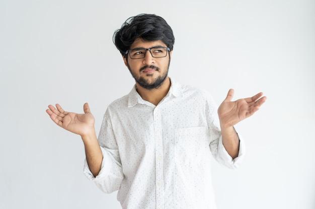 Verwirrter hübscher indischer mann, der arme zuckt und weg schaut.