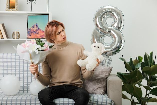 Verwirrter hübscher kerl am glücklichen frauentag, der blumenstrauß hält und teddybär in seiner hand betrachtet, der auf sofa im wohnzimmer sitzt