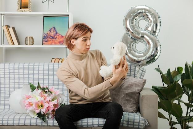 Verwirrter hübscher kerl am glücklichen frauentag, der den teddybären hält und betrachtet, der auf dem sofa im wohnzimmer sitzt