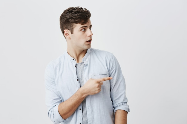 Verwirrter hübscher kerl mit stilvoller frisur, die mit unzufriedenem ausdruck seitwärts schaut, während er mit zeigefinger auf kopierraum zeigt. sieh dir das an!