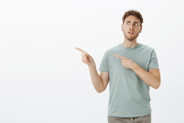 Verwirrter intensiver lustiger europäischer mann mit hellem haar, der mit zweifel schaut, während er nach links zeigt, unsicher ist und zögert Kostenlose Fotos