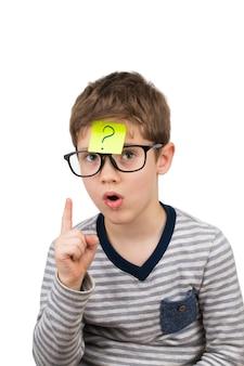 Verwirrter junge, der mit fragezeichen auf haftnotiz auf der stirn denkt