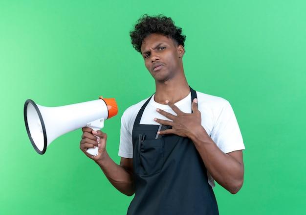 Verwirrter junger afroamerikanischer männlicher friseur, der uniform hält, die lautsprecher hält und hand auf herz lokalisiert auf grünem hintergrund setzt