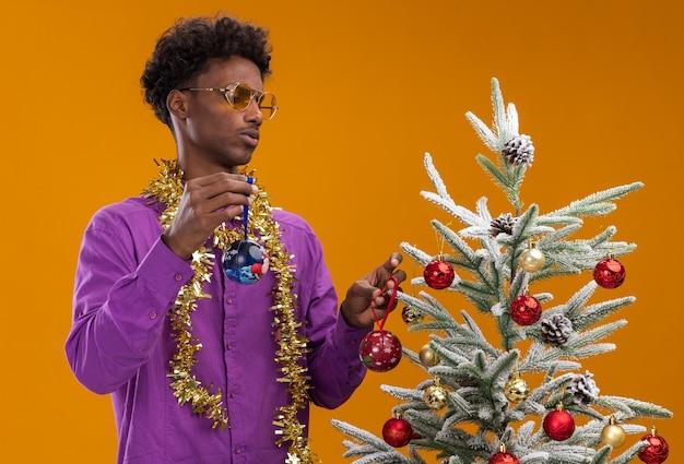 Verwirrter junger afroamerikanischer mann, der eine brille mit lametta-girlande um den hals trägt, der nahe verziertem weihnachtsbaum steht, der weihnachtskugeln hält, die baum lokalisiert auf orange wand betrachten