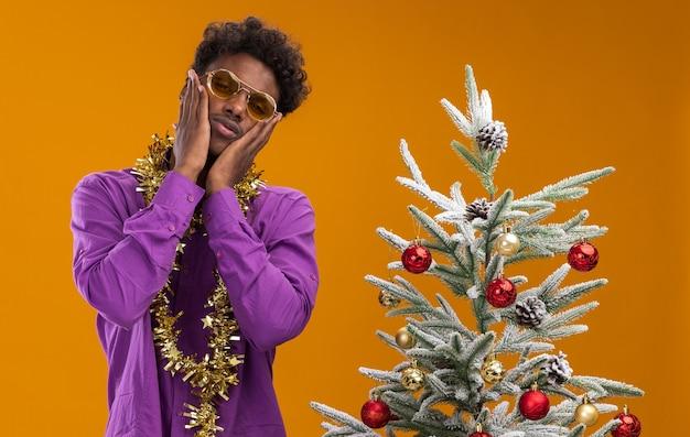 Verwirrter junger afroamerikanischer mann, der eine brille mit lametta-girlande um den hals trägt, die nahe verziertem weihnachtsbaum steht und hände auf gesicht lokalisiert auf orange wand hält