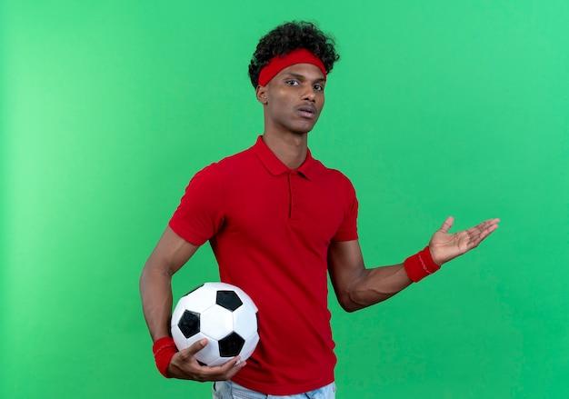Verwirrter junger afroamerikanischer sportlicher mann, der stirnband und armband hält, hält ball und zeigt mit der hand zur seite lokalisiert auf grünem hintergrund mit kopienraum