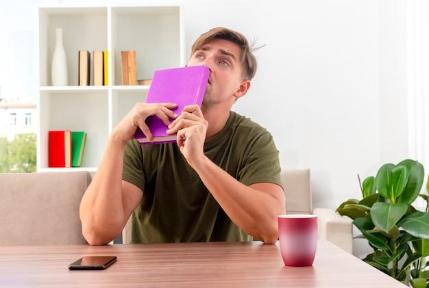 Verwirrter junger blonder gutaussehender mann sitzt am tisch mit telefon und tasse, die buch nahe am mund halten und im wohnzimmer nach oben schauen
