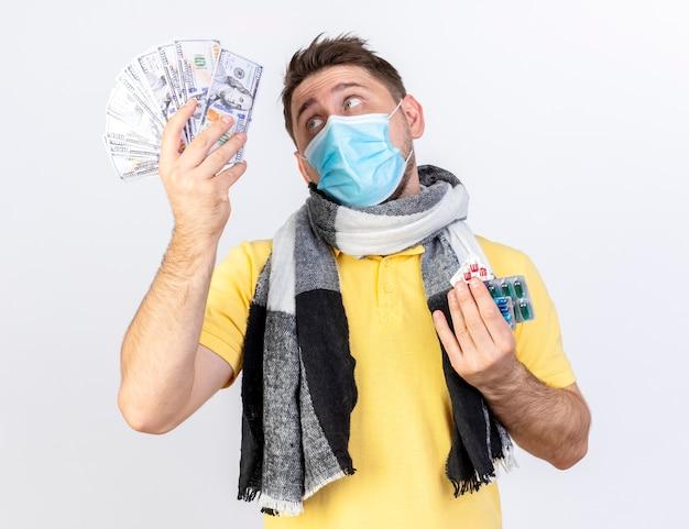 Verwirrter junger blonder kranker slawischer mann, der medizinische maske und schal trägt, hält geld und packungen von medizinischen pillen, die auf weißer wand mit kopienraum isoliert werden